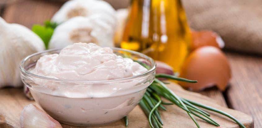 Das Grundrezept der Knoblauchmayonnaisebesteht aus Eigelb, Öl, Knoblauch sowie Salz und Pfeffer.